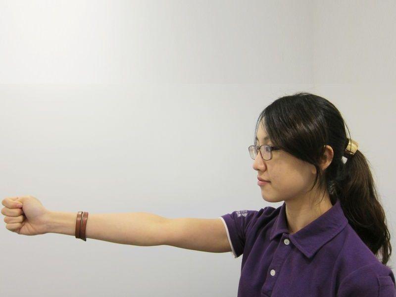 動作1:手臂伸直,大拇指彎曲,讓其他四指包住大拇指握拳,拳眼朝天花板