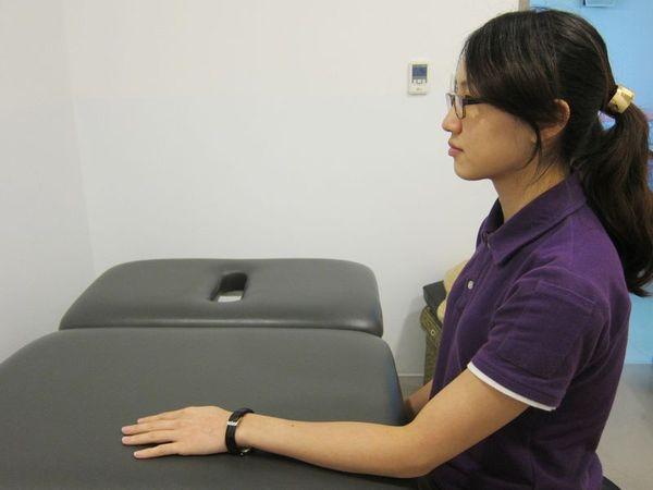 動作1:坐在椅子上,手臂慢慢地放在桌面,呈預備姿勢