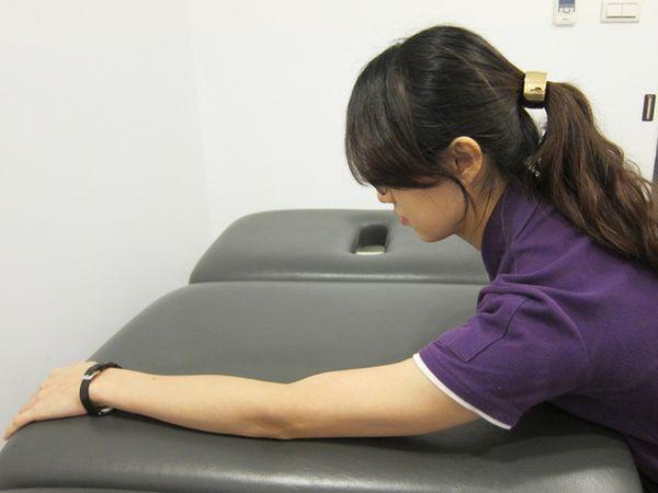 動作2:配合彎腰將手臂往前伸直沿桌面滑動向前伸直,當感到肩關節有緊實感時停留 15~30秒