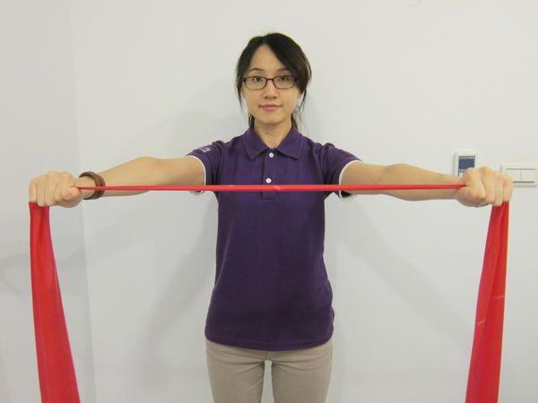 動作2:維持原姿勢,施力將彈力帶往兩邊平行拉開,大於肩寬。