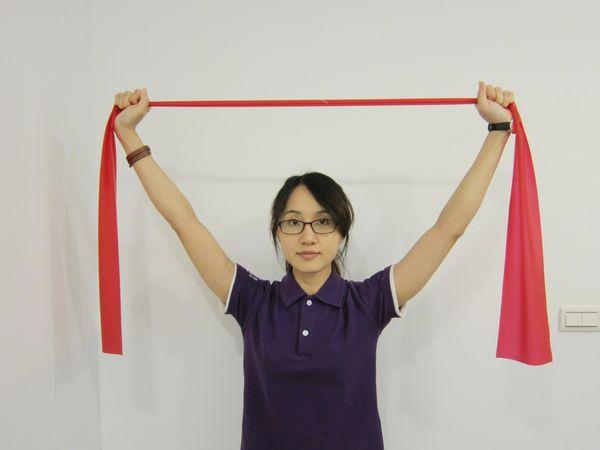 動作3:手臂維持打直與手握彈力帶姿勢,將雙手往上平舉。