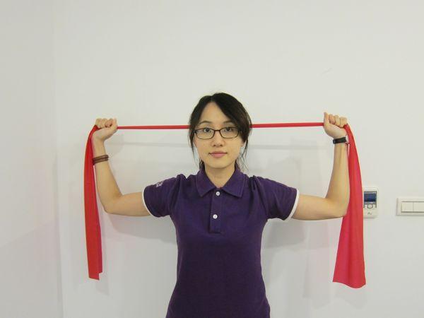 動作4:維持手握彈力帶姿勢將雙手同時往後伸展,讓彈力帶跨過頭上方