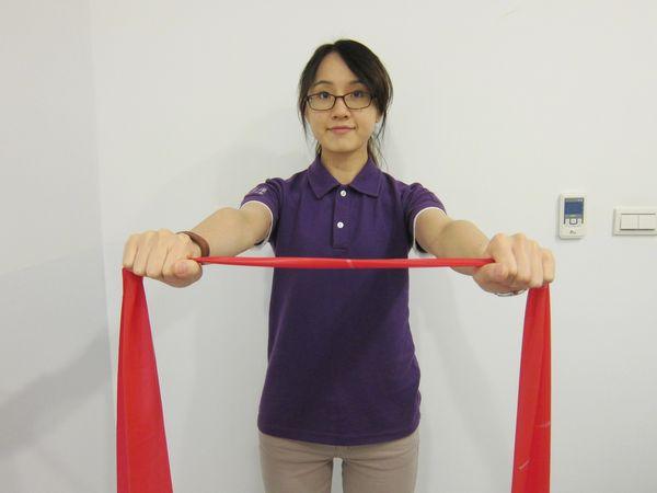 動作1:肩膀自然下垂,手臂往前打直,手握彈力帶(或用絲襪替代)與肩同寬,高度於胸前,做預備動作。